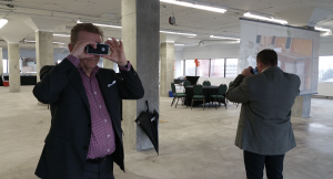 two realtors hold up VR for business viewers in an empty warehouse space