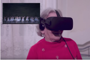 A female senior citizen uses a headset for VR travel to experience a distant ballet production.