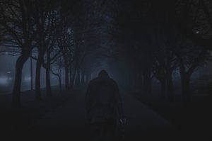 Man walking between trees at night.