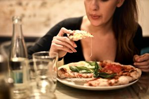 Woman eating pizza in a restaurant