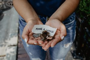 "A person holding change in their hands with a sign ""make a change"""